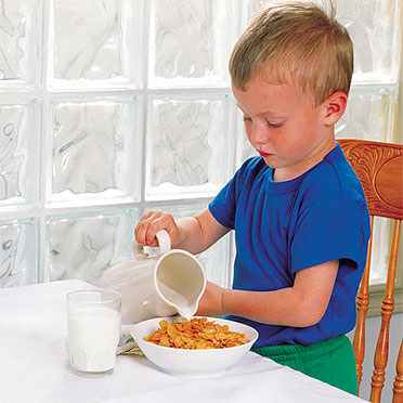 Child pouring milk on cereal